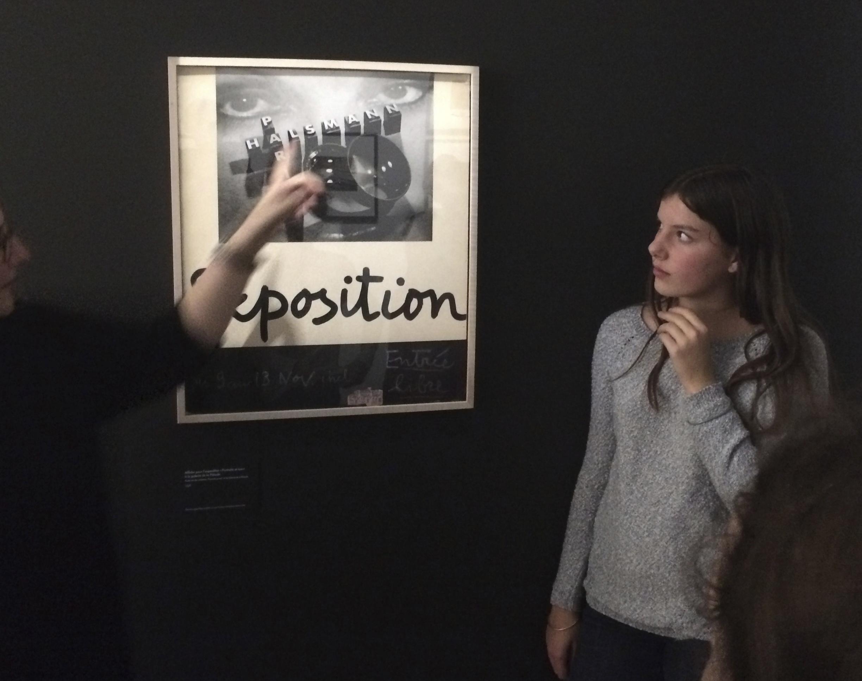 """Jeu de regards devant l'affiche de l'exposition """"Portraits et nus"""" organisée à la Galerie de la Pléiade en 1936"""